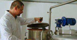 Trabajador de sexo masculino que comprueba el tanque de la destilación en la fábrica 4k almacen de video