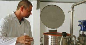 Trabajador de sexo masculino que comprueba el tanque de la destilación en la fábrica 4k almacen de metraje de vídeo
