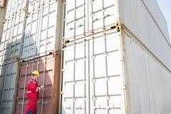 Trabajador de sexo masculino que examina los contenedores para mercancías mientras que escribe en el tablero en yarda de envío Fotos de archivo libres de regalías
