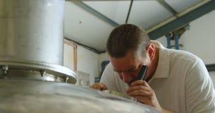 Trabajador de sexo masculino que examina un tanque 4k de la destilación almacen de metraje de vídeo