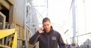 Trabajador de sexo masculino que habla en el teléfono móvil fuera del taller 4k