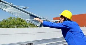 Trabajador de sexo masculino que habla en el teléfono móvil en la estación solar 4k
