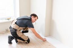 Trabajador de sexo masculino que instala el nuevo suelo laminado de madera en un piso caliente de la hoja de la película sistema  fotografía de archivo