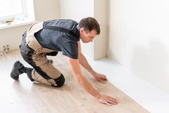 Trabajador de sexo masculino que instala el nuevo suelo laminado de madera en un piso caliente de la hoja de la película sistema  foto de archivo libre de regalías