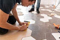 Trabajador de sexo masculino que instala el nuevo suelo laminado de madera La combinación de los paneles de madera de la lamina y fotos de archivo