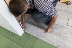 Trabajador de sexo masculino que instala el suelo laminado, hombre que instala el nuevo suelo laminado de madera Hombre que pone  fotos de archivo