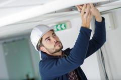 Trabajador de sexo masculino que lanza el panel de arriba del tejado imagen de archivo