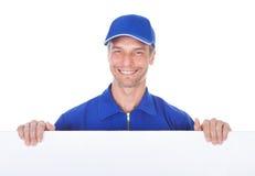 Trabajador de sexo masculino que lleva a cabo el cartel en blanco Imagen de archivo