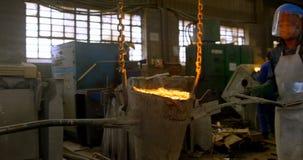 Trabajador de sexo masculino que lleva el metal fundido en el taller 4k almacen de metraje de vídeo