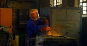 Trabajador de sexo masculino que mezcla el metal mudado en envase en el taller 4k metrajes