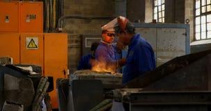 Trabajador de sexo masculino que quita el metal fundido del horno en el taller 4k almacen de video