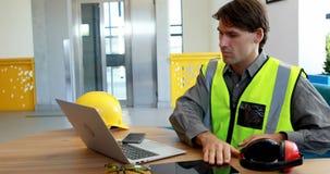 Trabajador de sexo masculino que usa el ordenador portátil y la tableta digital en el escritorio 4k