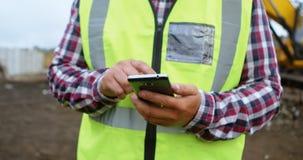 Trabajador de sexo masculino que usa el teléfono móvil en el depósito de chatarra 4k