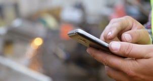 Trabajador de sexo masculino que usa el teléfono móvil en el depósito de chatarra 4k metrajes
