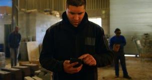 Trabajador de sexo masculino que usa el teléfono móvil en el taller 4k