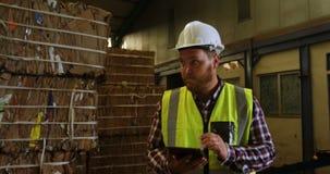 Trabajador de sexo masculino que usa la tableta digital 4k almacen de video