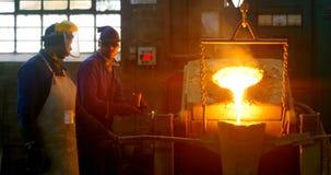Trabajador de sexo masculino que vierte el metal fundido en molde en el taller 4k almacen de video