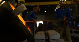 Trabajador de sexo masculino que vierte el metal fundido en molde en el taller 4k metrajes