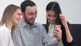 Trabajador de sexo masculino de risa y dos compañeros de trabajo femeninos que toman selfies en la oficina Imágenes de archivo libres de regalías