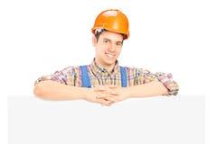 Trabajador de sexo masculino satisfecho que se coloca detrás del panel Imagenes de archivo