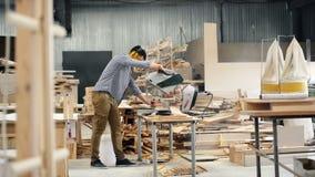 Trabajador de sexo masculino usando la sierra eléctrica en la madera que asierra del taller de madera que trabaja solamente almacen de video