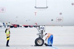 Trabajador de tierra del aeropuerto que comprueba el avión Imagen de archivo libre de regalías