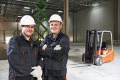 Trabajador de Warehouse delante de la carretilla elevadora Fotografía de archivo libre de regalías