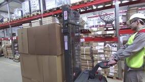 Trabajador de Warehouse en la carretilla elevadora industrial metrajes