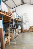Trabajador de Warehouse que carga para arriba la plataforma fotografía de archivo libre de regalías