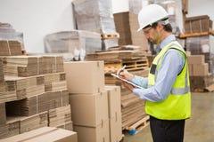 Trabajador de Warehouse que comprueba su lista en el tablero fotos de archivo