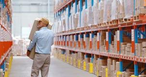 Trabajador de Warehouse que lleva a cabo los paquetes almacen de metraje de vídeo
