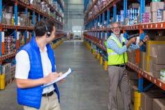 Trabajador de Warehouse que obra recíprocamente con uno a fotografía de archivo