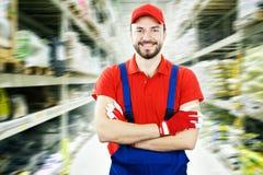 Trabajador de Warehouse que se coloca entre los estantes fotos de archivo