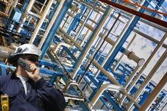 Trabajador del aceite con las construcciones de las tuberías Fotografía de archivo libre de regalías