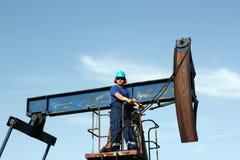 Trabajador del aceite que se coloca en el enchufe de la bomba fotos de archivo