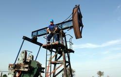 Trabajador del aceite que se coloca en el enchufe de la bomba Foto de archivo libre de regalías