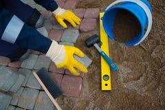 Trabajador del albañil que hace el pavimento de la acera Foto de archivo