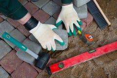 Trabajador del albañil que hace el pavimento de la acera Fotografía de archivo