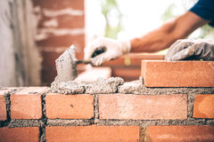 Trabajador del albañil que instala la albañilería del ladrillo en la pared exterior con el cuchillo de masilla de la paleta fotografía de archivo libre de regalías