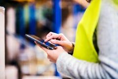 Trabajador del almacén de la mujer con la tableta Foto de archivo libre de regalías