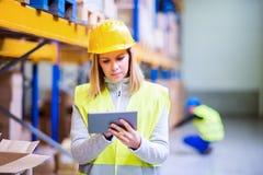 Trabajador del almacén de la mujer con la tableta Imagen de archivo libre de regalías