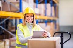 Trabajador del almacén de la mujer con la tableta Imágenes de archivo libres de regalías