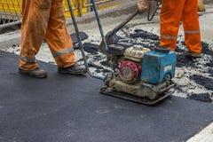 Trabajador del asfalto con la placa 5 del compresor Imágenes de archivo libres de regalías