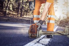 Trabajador del camino que comienza un brushcutter Fotos de archivo libres de regalías