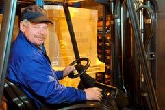 Trabajador del cargador de la carretilla elevadora en el almacén Imágenes de archivo libres de regalías