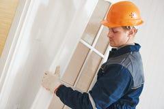 Trabajador del carpintero en la instalación de la puerta imagenes de archivo