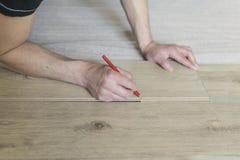 Trabajador del carpintero que instala el suelo laminado en el cuarto Fotografía de archivo