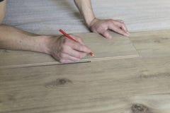 Trabajador del carpintero que instala el suelo laminado en el cuarto Imágenes de archivo libres de regalías