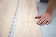 Trabajador del carpintero que instala el suelo laminado en el cuarto foto de archivo