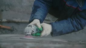 Trabajador del constructor con el muro de cemento del acabamiento del corte de máquina de la amoladora en el emplazamiento de la  almacen de metraje de vídeo